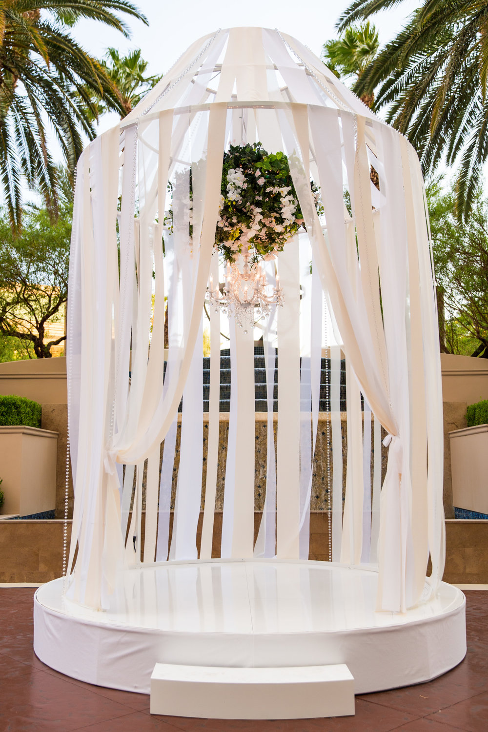 The wedding ceremony took place in a larger than life birdcage wrapped in ribbon with a floral chandelier hanging in the center.  Wedding Planning by  Andrea Eppolito Events   ·  Photography by  Shandro Photo    ·  Wedding Venue  Four Seasons Las Vegas   ·  Floral and Decor by  Destination by Design   ·  Chandeliers and Lighting by  LED Unplugged