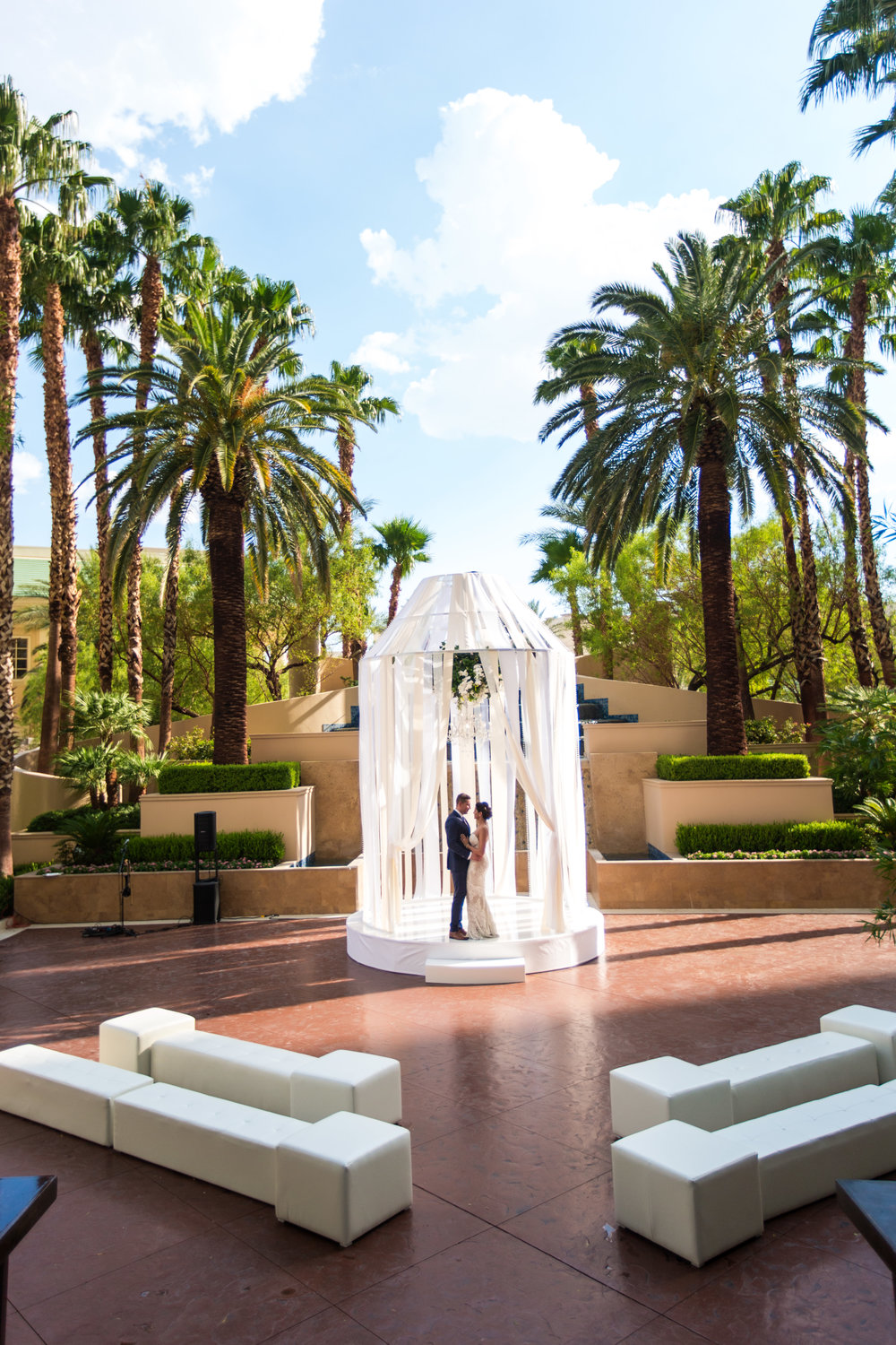 Bride and groom at ceremony location.  Wedding Planning by  Andrea Eppolito Events   ·  Photography by  Shandro Photo    ·  Wedding Venue  Four Seasons Las Vegas   ·  Floral and Decor by  Destination by Design   ·  Cake by  Four Seasons Las Vegas   ·  Chandeliers and Lighting by  LED Unplugged   ·  Dress by  Berta