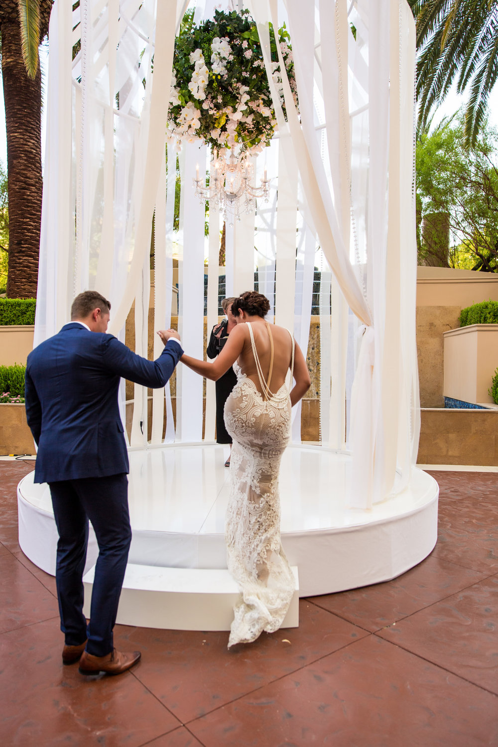 The bride and groom walked into the ceremony together.  Wedding Planning by  Andrea Eppolito Events   ·  Photography by  Shandro Photo    ·  Wedding Venue  Four Seasons Las Vegas   ·  Floral and Decor by  Destination by Design   ·  Cake by  Four Seasons Las Vegas   ·  Chandeliers and Lighting by  LED Unplugged   ·  Dress by  Berta
