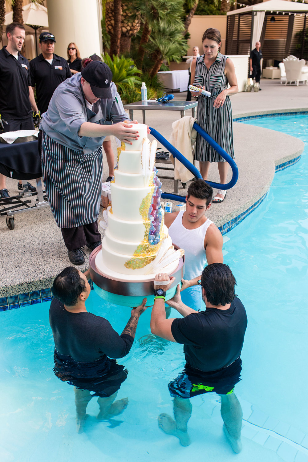 Loading In the Wedding Cake. Wedding Planning by  Andrea Eppolito Events   ·  Photography by  Shandro Photo    ·  Wedding Venue  Four Seasons Las Vegas   ·  Floral and Decor by  Destination by Design   ·  Cake by  Four Seasons Las Vegas   ·  Chandeliers and Lighting by  LED Unplugged   ·  Dress by  Berta