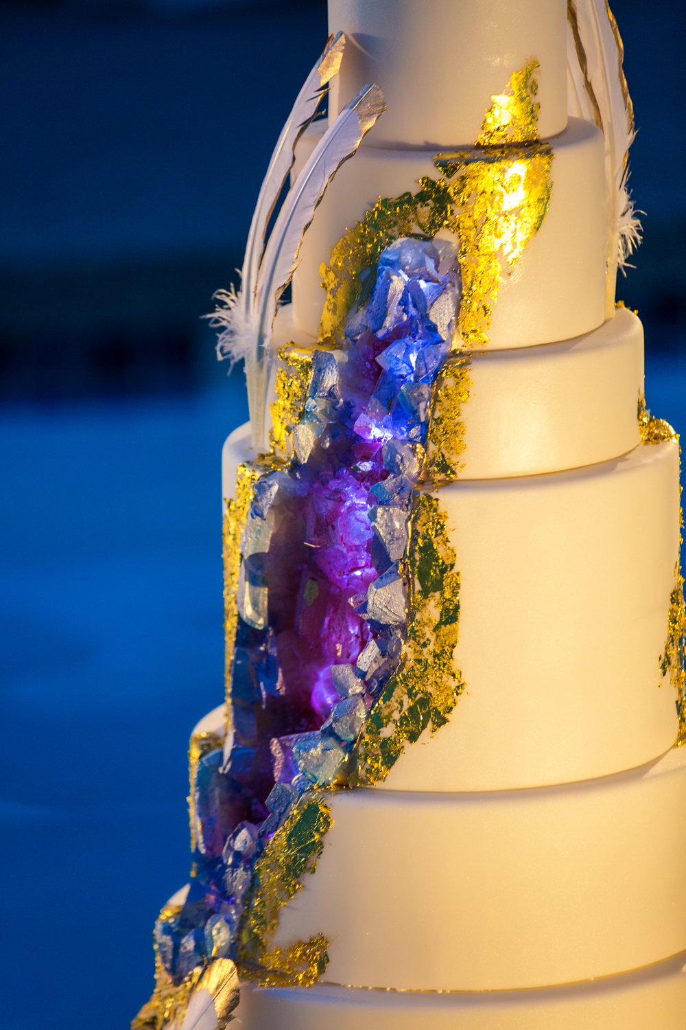 Geode cake with feathers. Jewel toned wedding centerpieces with gold accents. Wedding Planning by  Andrea Eppolito Events   ·  Photography by  Shandro Photo    ·  Wedding Venue  Four Seasons Las Vegas   ·  Floral and Decor by  Destination by Design   ·  Cake by  Four Seasons Las Vegas   ·  Chandeliers and Lighting by  LED Unplugged   ·  Dress by  Berta   and Menu by Alligator Soup