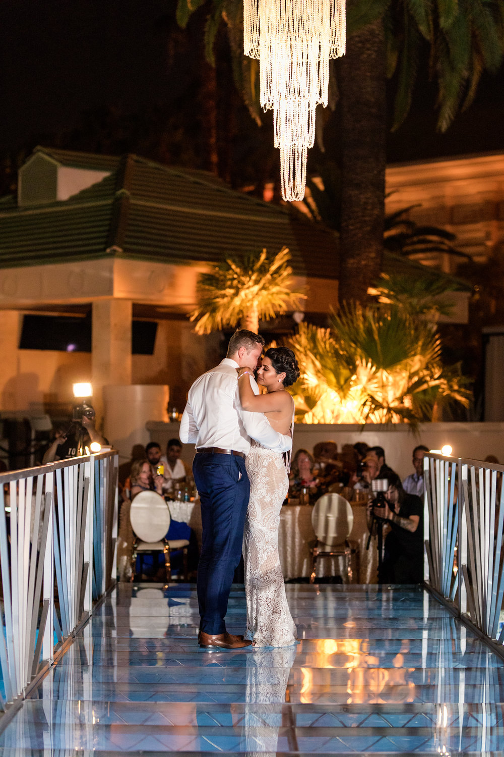 First dance on bridge over pool. Jewel toned wedding centerpieces with gold accents. Wedding Planning by  Andrea Eppolito Events   ·  Photography by  Shandro Photo    ·  Wedding Venue  Four Seasons Las Vegas   ·  Floral and Decor by  Destination by Design   ·  Cake by  Four Seasons Las Vegas   ·  Chandeliers and Lighting by  LED Unplugged   ·  Dress by  Berta   and Menu by Alligator Soup