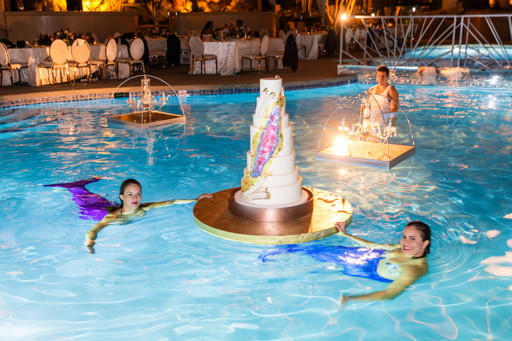 Geode Wedding cake brought to the edge by mermaids. First dance on bridge over pool. Jewel toned wedding centerpieces with gold accents. Wedding Planning by  Andrea Eppolito Events   ·  Photography by  Shandro Photo    ·  Wedding Venue  Four Seasons Las Vegas   ·  Floral and Decor by  Destination by Design   ·  Cake by  Four Seasons Las Vegas   ·  Chandeliers and Lighting by  LED Unplugged   ·  Dress by  Berta   and Menu by Alligator Soup