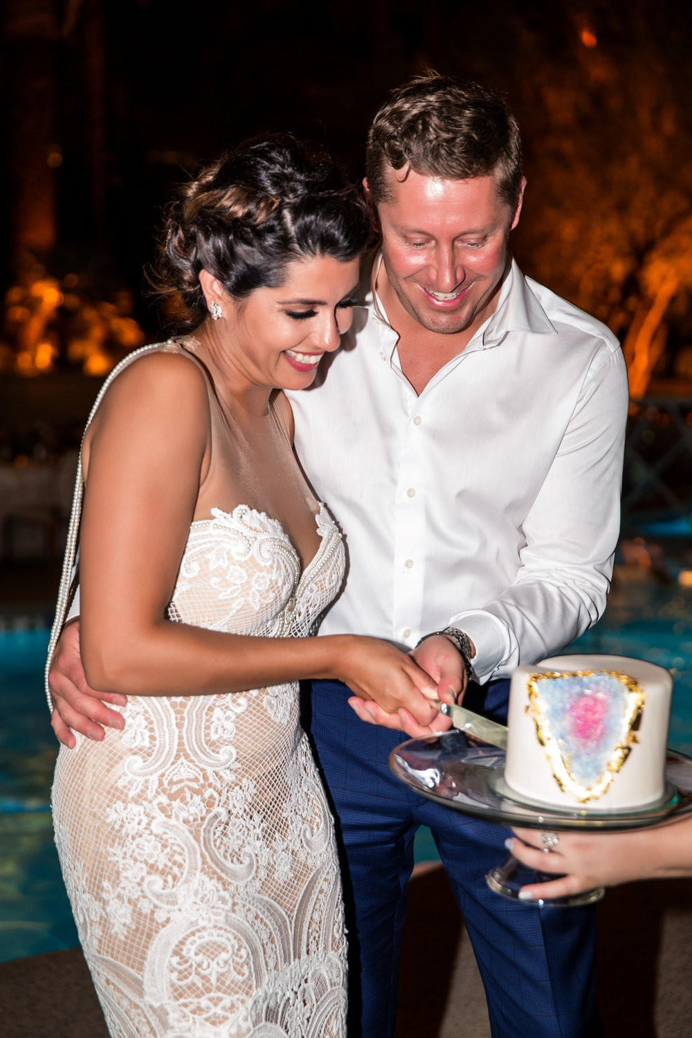 Cutting the top tier of the wedding cake. First dance on bridge over pool. Jewel toned wedding centerpieces with gold accents. Wedding Planning by  Andrea Eppolito Events   ·  Photography by  Shandro Photo    ·  Wedding Venue  Four Seasons Las Vegas   ·  Floral and Decor by  Destination by Design   ·  Cake by  Four Seasons Las Vegas   ·  Chandeliers and Lighting by  LED Unplugged   ·  Dress by  Berta   and Menu by Alligator Soup