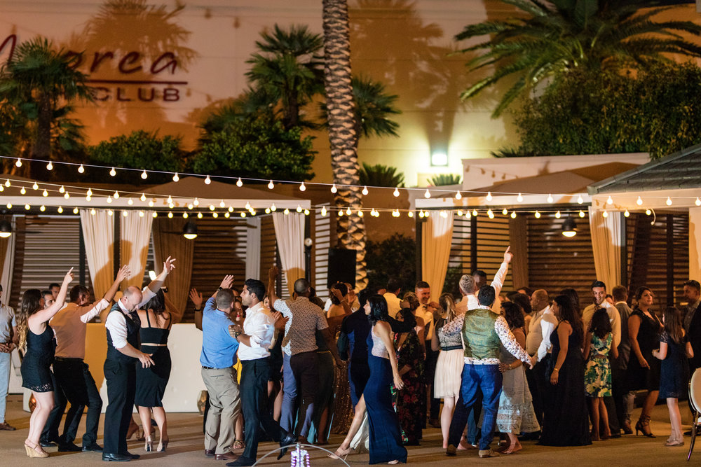 Dance Party on the pool deck. Wedding Planning by  Andrea Eppolito Events   ·  Photography by  Shandro Photo    ·  Wedding Venue  Four Seasons Las Vegas   ·  Floral and Decor by  Destination by Design   ·  Cake by  Four Seasons Las Vegas   ·  Chandeliers and Lighting by  LED Unplugged   ·  Dress by  Berta   and Menu by Alligator Soup