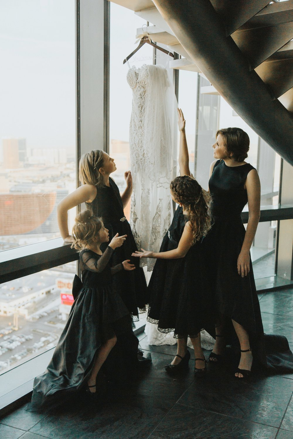 Bridesmaids looking at wedding dress
