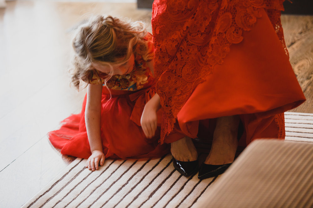 Flower girl helping bride into her black Louboutin shoes. Luxury wedding at the Mandarin Oriental with a color scheme of white, blush, and pops of wine red produced by Las Vegas Wedding Planner Andrea Eppolito with photos by Stephen Salazar Photography.