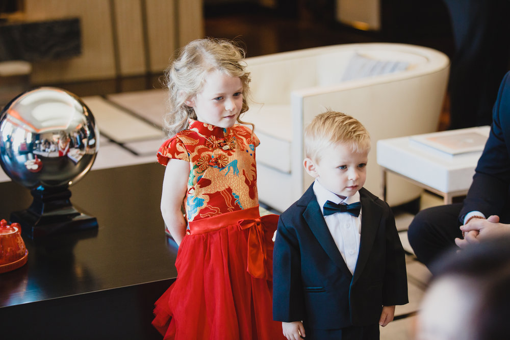 Two children in Chinese Tea Ceremony.  Luxury wedding at the Mandarin Oriental with a color scheme of white, blush, and pops of wine red produced by Las Vegas Wedding Planner Andrea Eppolito with photos by Stephen Salazar Photography.