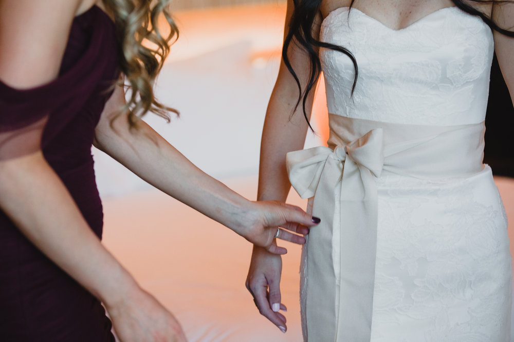 Tie bow on belt for Vera Wang Wedding Dress.  Luxury wedding at the Mandarin Oriental with a color scheme of white, blush, and pops of wine red produced by Las Vegas Wedding Planner Andrea Eppolito with photos by Stephen Salazar Photography.