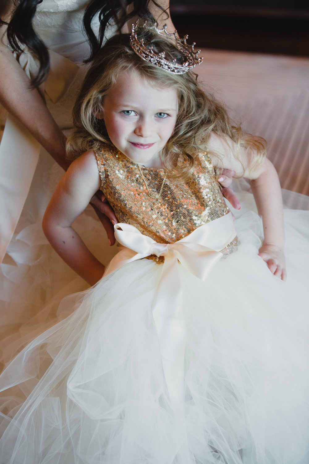 Princess crown on flower girl. Luxury wedding at the Mandarin Oriental with a color scheme of white, blush, and pops of wine red produced by Las Vegas Wedding Planner Andrea Eppolito with photos by Stephen Salazar Photography.