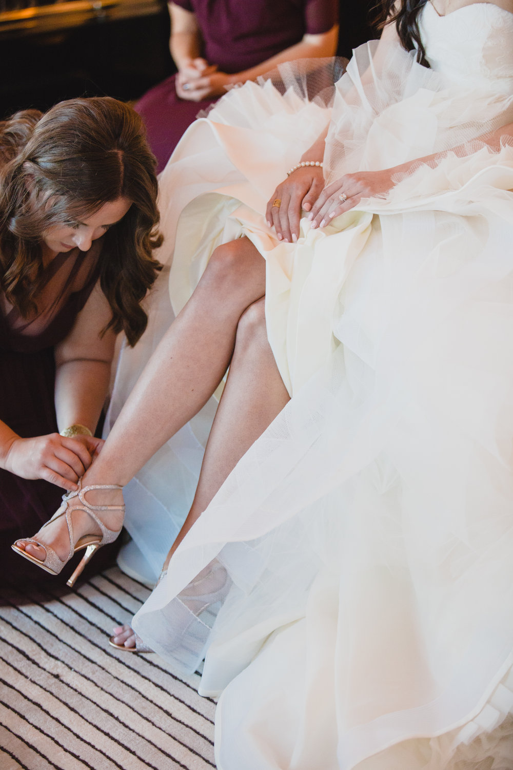 Putting on Jimmy Choo Wedding Shoes.  Luxury wedding at the Mandarin Oriental with a color scheme of white, blush, and pops of wine red produced by Las Vegas Wedding Planner Andrea Eppolito with photos by Stephen Salazar Photography.