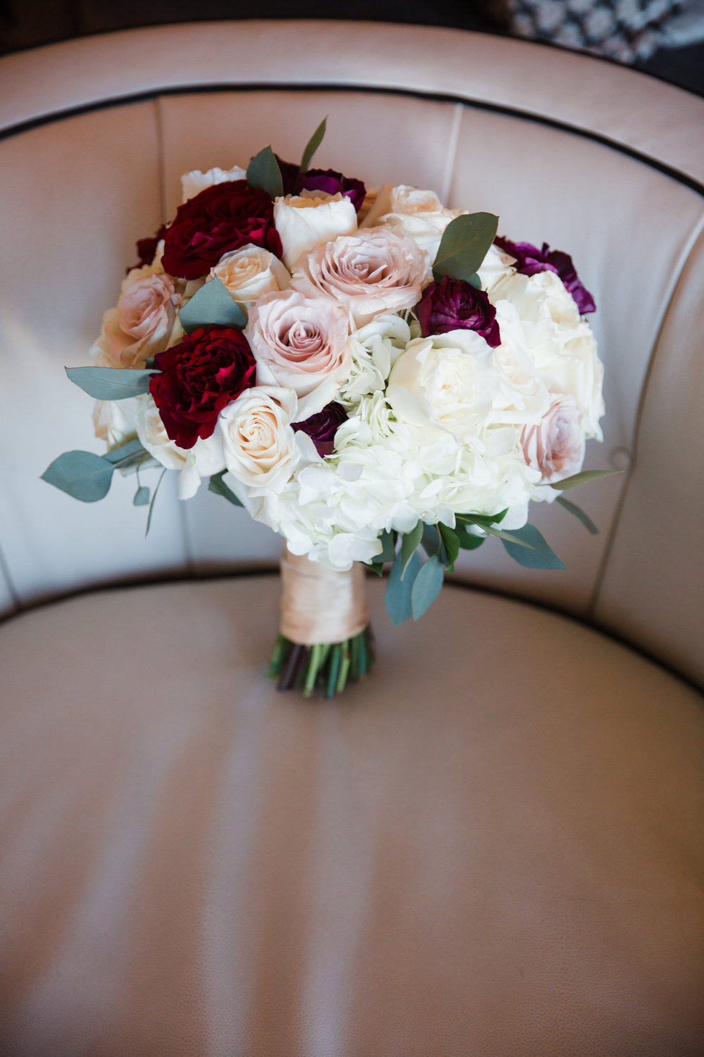 Deep Red and Blush Wedding Bouquet.  Luxury wedding at the Mandarin Oriental with a color scheme of white, blush, and pops of wine red produced by Las Vegas Wedding Planner Andrea Eppolito with photos by Stephen Salazar Photography.
