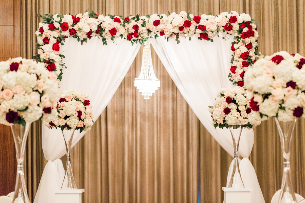 Wedding Ceremony Chuppah with dark red, blush, and white color scheme.  Luxury wedding at the Mandarin Oriental with a color scheme of white, blush, and pops of wine red produced by Las Vegas Wedding Planner Andrea Eppolito with photos by Stephen Salazar Photography.