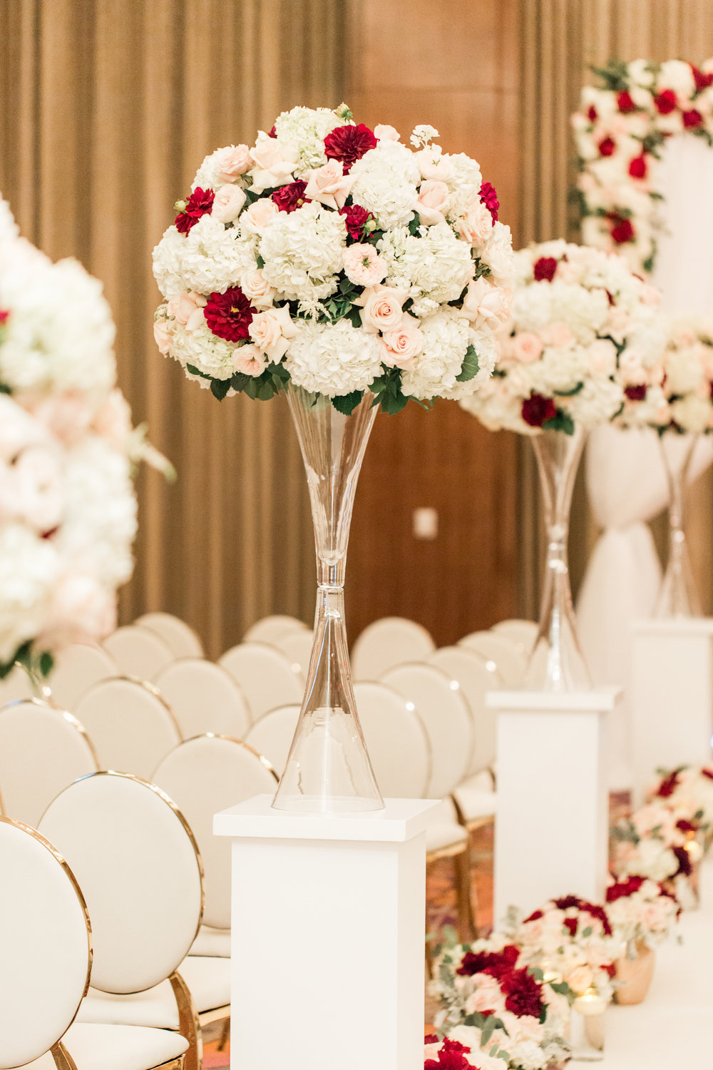 Wedding ceremony aisle markers in lush wedding ceremony.  Luxury wedding at the Mandarin Oriental with a color scheme of white, blush, and pops of wine red produced by Las Vegas Wedding Planner Andrea Eppolito with photos by Stephen Salazar Photography.