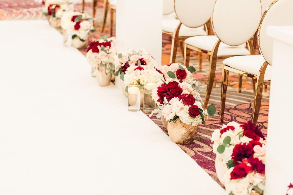 Low red and blush wedding ceremony aisle details.  Luxury wedding at the Mandarin Oriental with a color scheme of white, blush, and pops of wine red produced by Las Vegas Wedding Planner Andrea Eppolito with photos by Stephen Salazar Photography.