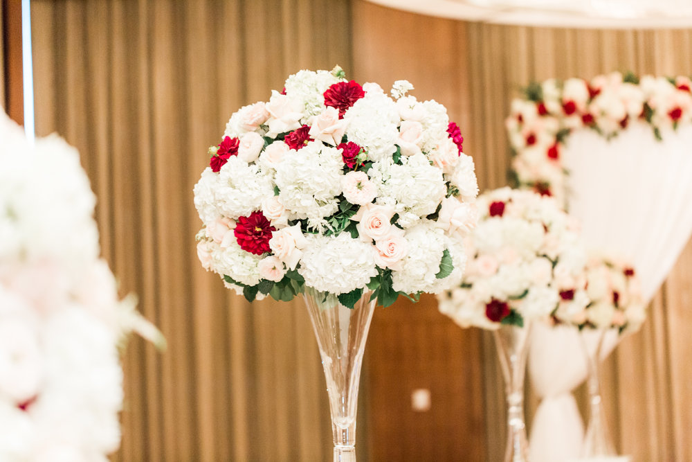 red and white wedding flowers.  Luxury wedding at the Mandarin Oriental with a color scheme of white, blush, and pops of wine red produced by Las Vegas Wedding Planner Andrea Eppolito with photos by Stephen Salazar Photography.