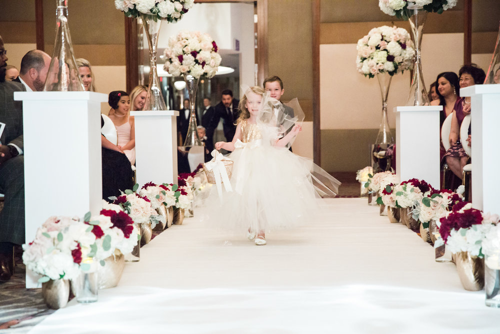 flower girl in ivory tulle and gold. Luxury wedding at the Mandarin Oriental with a color scheme of white, blush, and pops of wine red produced by Las Vegas Wedding Planner Andrea Eppolito with photos by Stephen Salazar Photography.