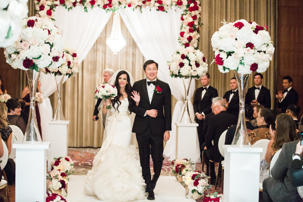 Wedding Recessional.  Luxury wedding at the Mandarin Oriental with a color scheme of white, blush, and pops of wine red produced by Las Vegas Wedding Planner Andrea Eppolito with photos by Stephen Salazar Photography.