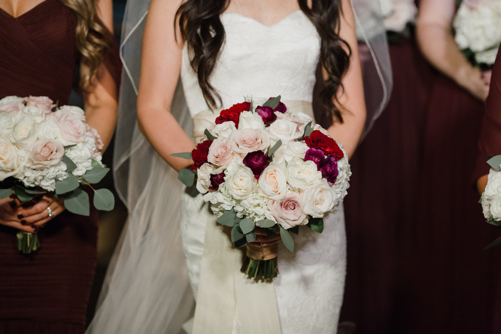 Ivory and oxblood wedding colors with bridal bouquet.  Luxury wedding at the Mandarin Oriental with a color scheme of white, blush, and pops of wine red produced by Las Vegas Wedding Planner Andrea Eppolito with photos by Stephen Salazar Photography.