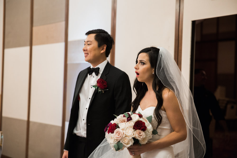 Reception reveal.  Bride and groom see the wedding for the first time.  Luxury wedding at the Mandarin Oriental with a color scheme of white, blush, and pops of wine red produced by Las Vegas Wedding Planner Andrea Eppolito with photos by Stephen Salazar Photography.