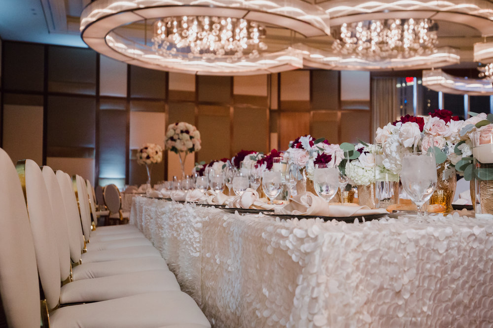 Long banquet tables with flutter linens with flowers in pink, ivory, and pops of deep red.  Luxury wedding at the Mandarin Oriental with a color scheme of white, blush, and pops of wine red produced by Las Vegas Wedding Planner Andrea Eppolito with photos by Stephen Salazar Photography.