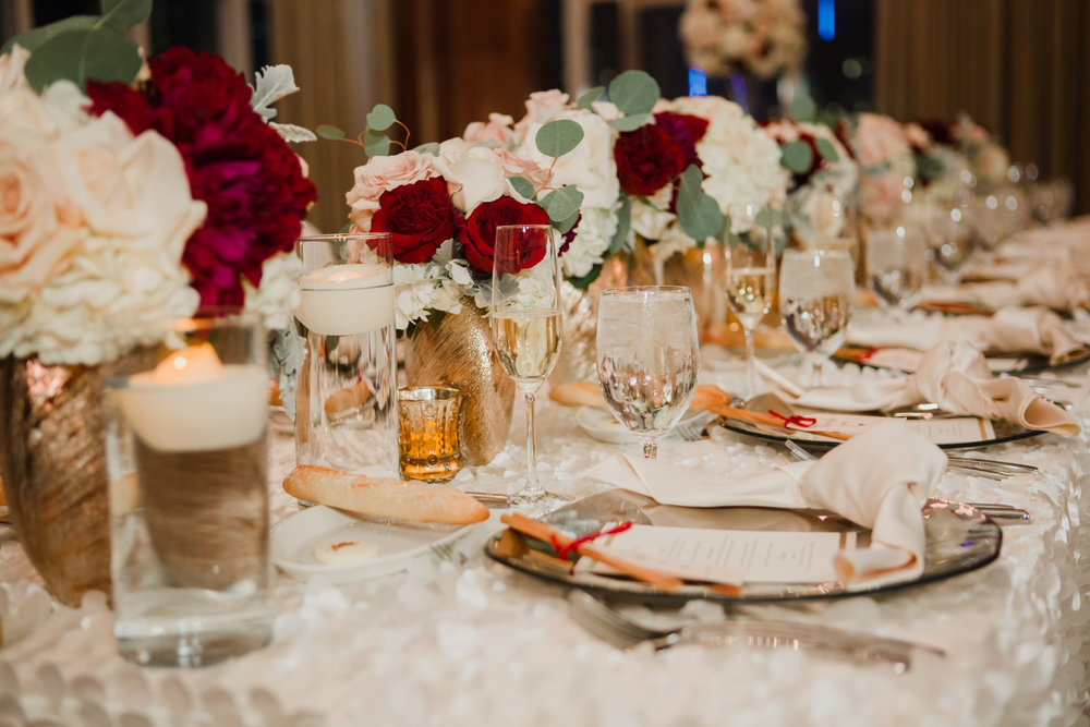 Long, low wedding centerpieces in red and rose.  Luxury wedding at the Mandarin Oriental with a color scheme of white, blush, and pops of wine red produced by Las Vegas Wedding Planner Andrea Eppolito with photos by Stephen Salazar Photography.
