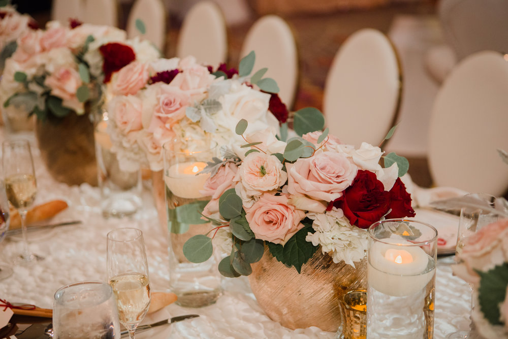 Blush roses in gold vase.  Luxury wedding at the Mandarin Oriental with a color scheme of white, blush, and pops of wine red produced by Las Vegas Wedding Planner Andrea Eppolito with photos by Stephen Salazar Photography.