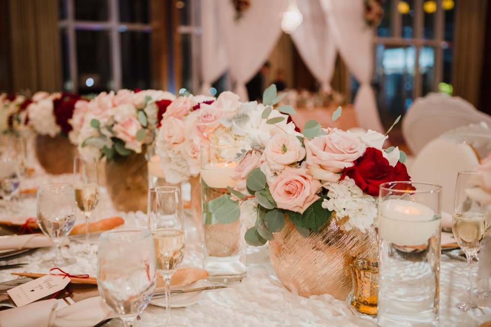 Pink roses with pops of red in gold vases.  Luxury wedding at the Mandarin Oriental with a color scheme of white, blush, and pops of wine red produced by Las Vegas Wedding Planner Andrea Eppolito with photos by Stephen Salazar Photography.