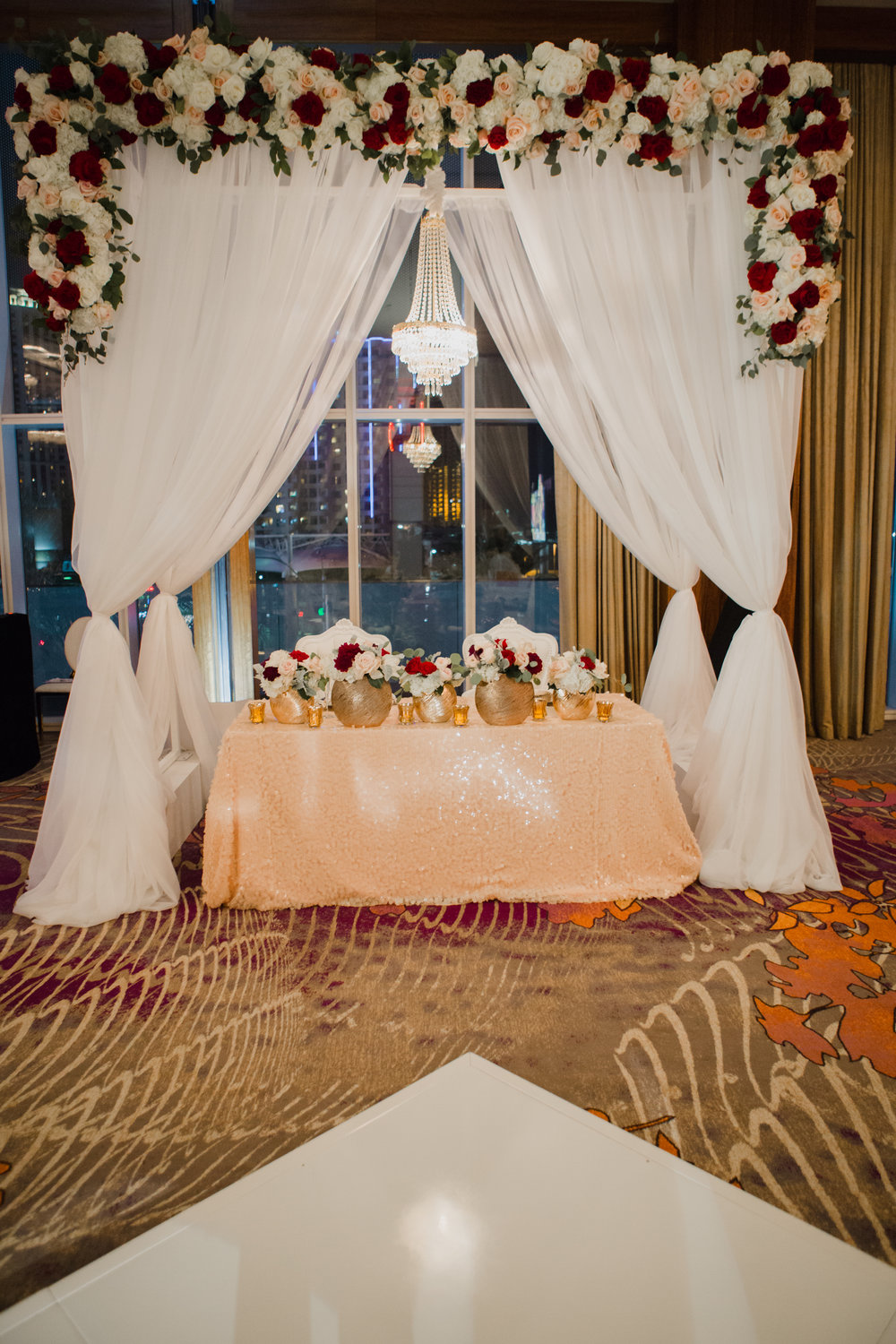 Sweetheart table under beautiful arch with lush floral garland.  Luxury wedding at the Mandarin Oriental with a color scheme of white, blush, and pops of wine red produced by Las Vegas Wedding Planner Andrea Eppolito with photos by Stephen Salazar Photography.