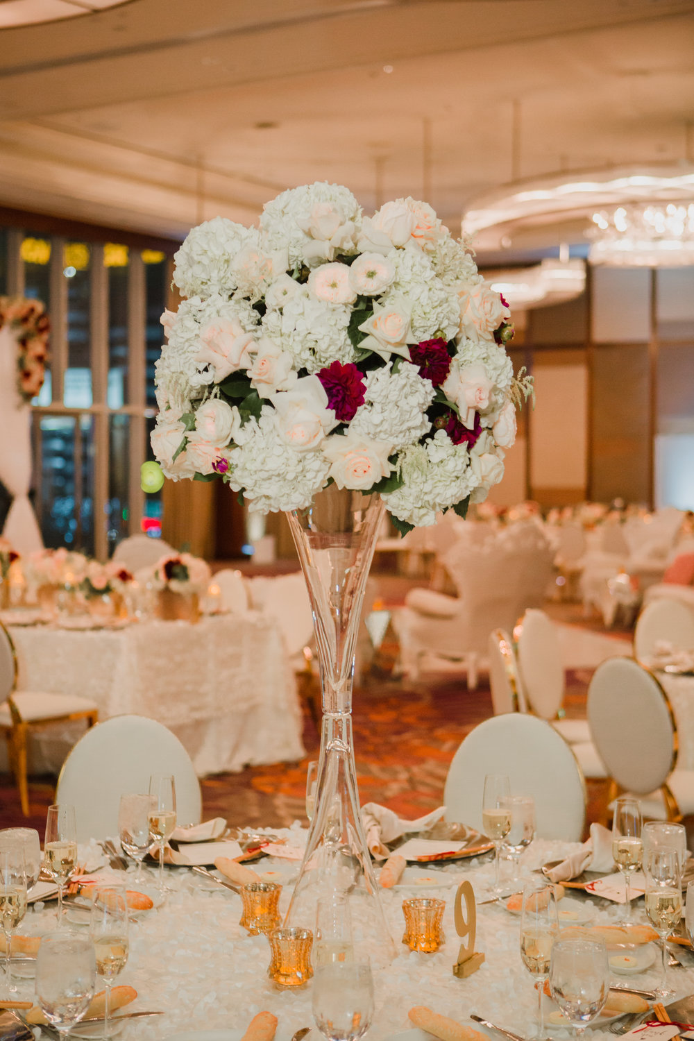 White hydrangea with pink roses and red dahlias.  Luxury wedding at the Mandarin Oriental with a color scheme of white, blush, and pops of wine red produced by Las Vegas Wedding Planner Andrea Eppolito with photos by Stephen Salazar Photography.
