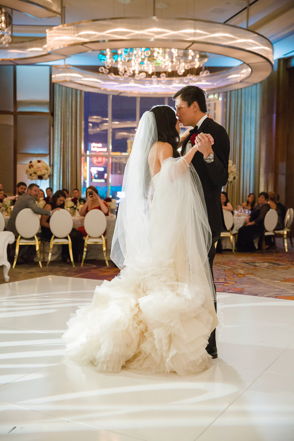 First dance on high gloss white dance floor.  Bride in Vera Wang with beautiful veil.  Luxury wedding at the Mandarin Oriental with a color scheme of white, blush, and pops of wine red produced by Las Vegas Wedding Planner Andrea Eppolito with photos by Stephen Salazar Photography.