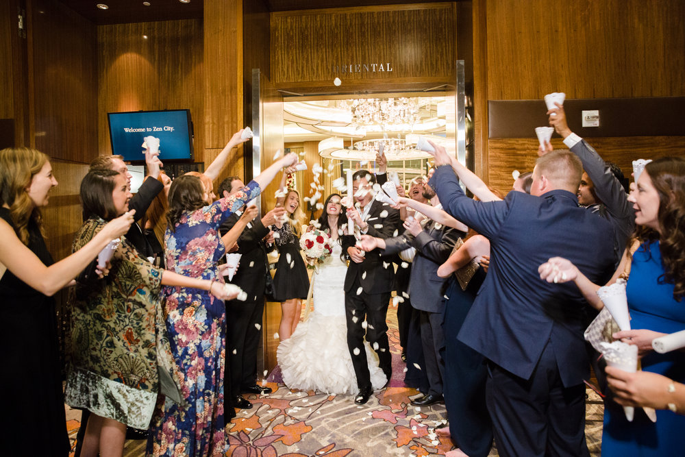Guests throwing rose petals during bride and groom's exit.  Luxury wedding at the Mandarin Oriental with a color scheme of white, blush, and pops of wine red produced by Las Vegas Wedding Planner Andrea Eppolito with photos by Stephen Salazar Photography.
