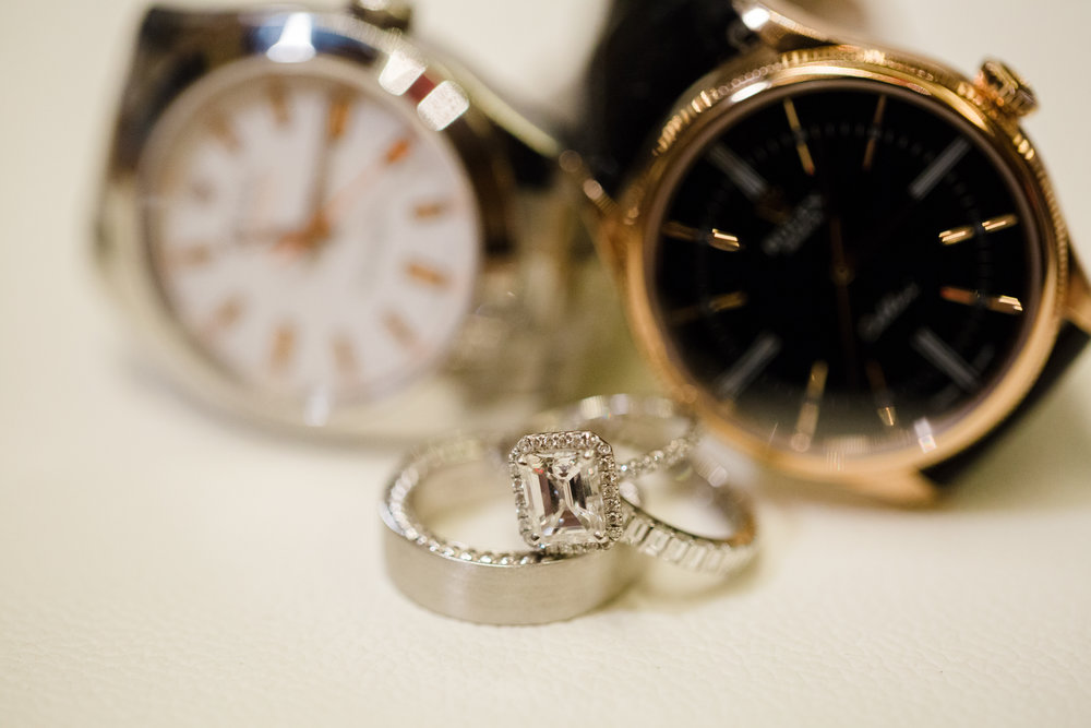 Wedding rings with his and hers rolex watches. Luxury wedding at the Mandarin Oriental with a color scheme of white, blush, and pops of wine red produced by Las Vegas Wedding Planner Andrea Eppolito with photos by Stephen Salazar Photography.