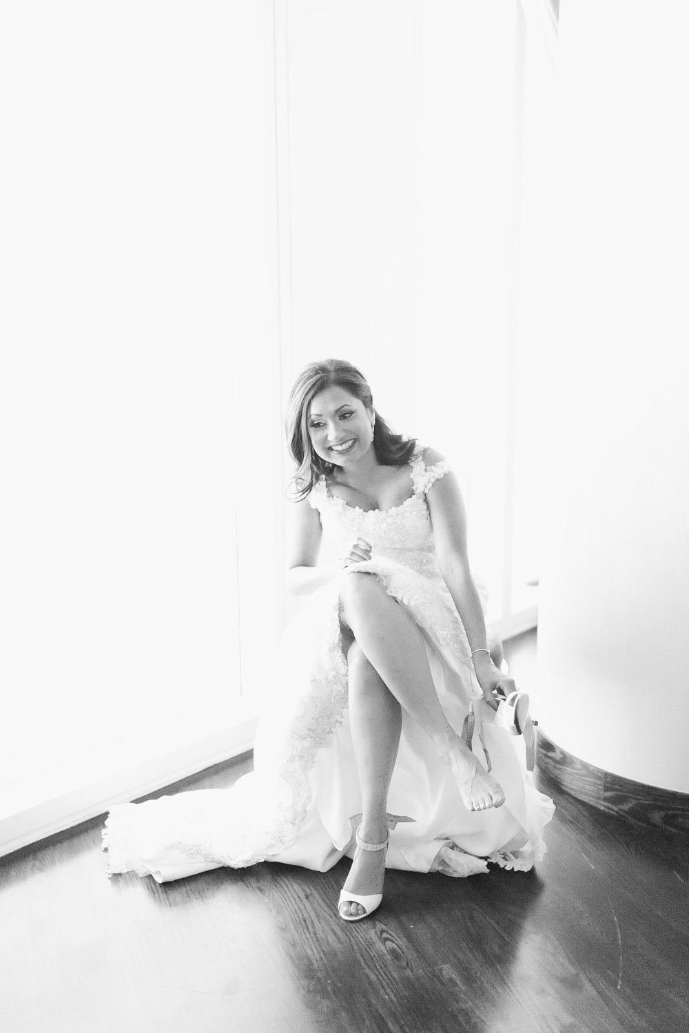 Black and white image of bride putting on her wedding shoes  Las Vegas Wedding Planner Andrea Eppolito shares this multicultural wedding.  Photo by J.Anne Photography.