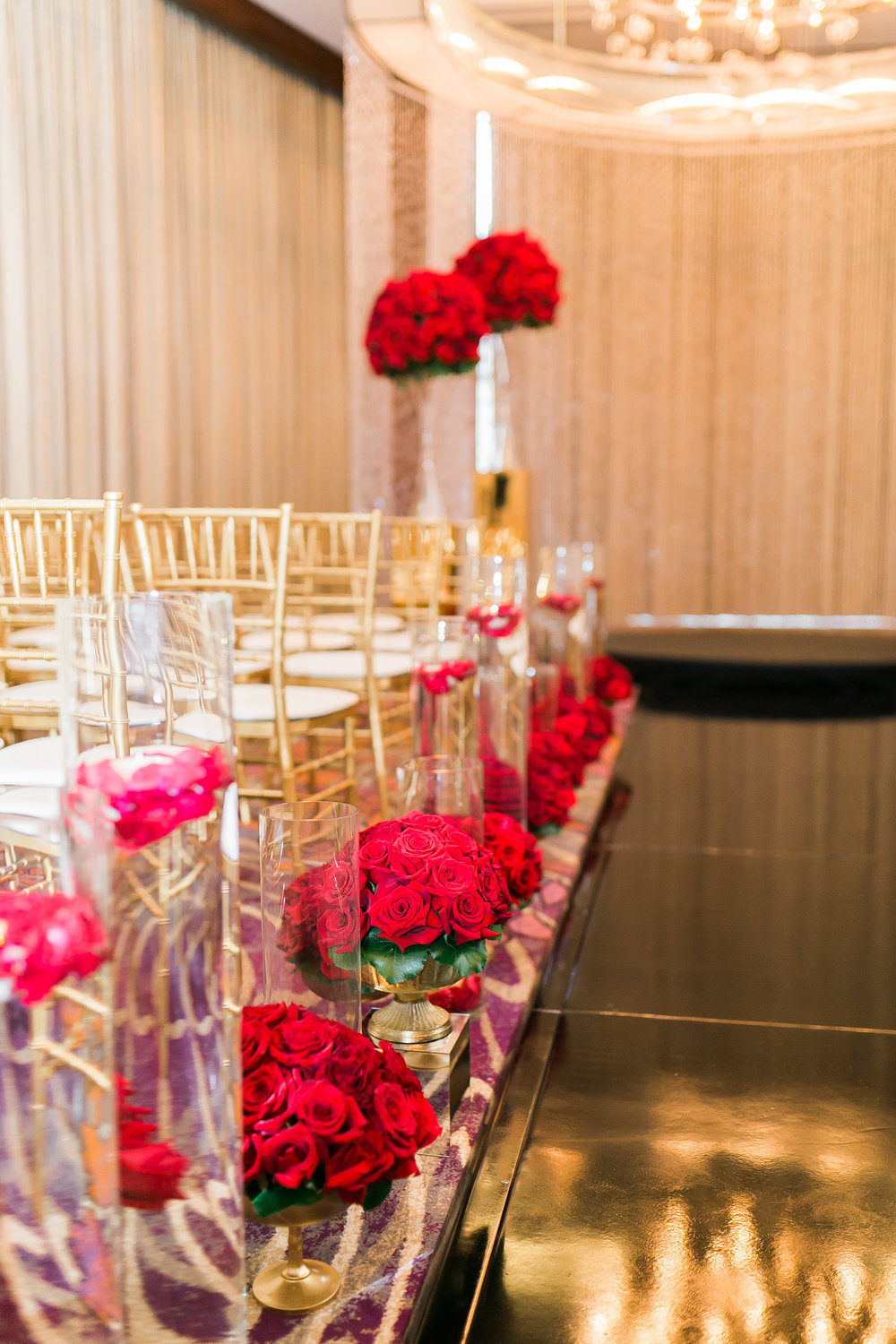 Small red rose centerpieces lined the high gloss black aisle.   Las Vegas Wedding Planner Andrea Eppolito shares this multicultural wedding.  Photo by J.Anne Photography. Wedding at Mandarin Oriental Las Vegas.  Decor by DBD Vegas.