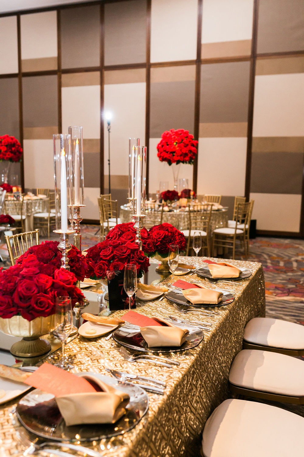 Long table with candelabras and gold linens, topped with red roses.  Las Vegas Wedding Planner Andrea Eppolito shares this multicultural wedding.  Photo by J.Anne Photography. Wedding at Mandarin Oriental Las Vegas.  Decor by DBD Vegas.