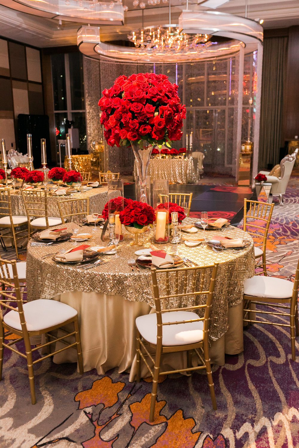 Tall centerpieces with red roses topped round centerpieces with gold linens.  Las Vegas Wedding Planner Andrea Eppolito shares this multicultural wedding.  Photo by J.Anne Photography. Wedding at Mandarin Oriental Las Vegas.  Decor by DBD Vegas.