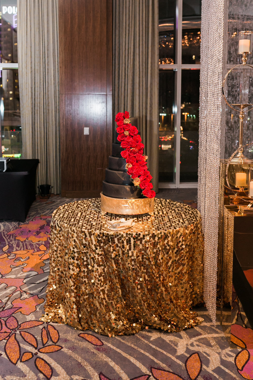 Black wedding cake with red roses.  Las Vegas Wedding Planner Andrea Eppolito shares this multicultural wedding.  Photo by J.Anne Photography. Wedding at Mandarin Oriental Las Vegas.  Decor by DBD Vegas.