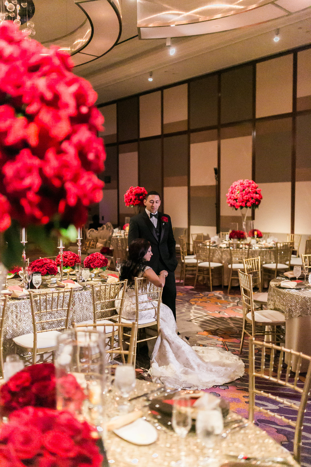 Bride and groom framed by red roses.  Las Vegas Wedding Planner Andrea Eppolito shares this multicultural wedding.  Photo by J.Anne Photography. Wedding at Mandarin Oriental Las Vegas.  Decor by DBD Vegas.