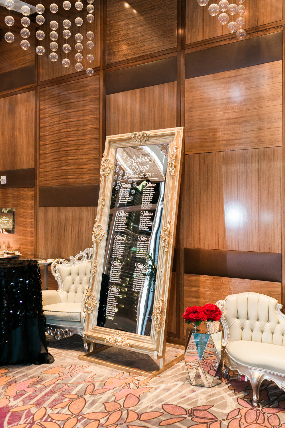 Guests found their seats on a mirrored escort card wall.  Las Vegas Wedding Planner Andrea Eppolito shares this multicultural wedding.  Photo by J.Anne Photography. Wedding at Mandarin Oriental Las Vegas.  Decor by DBD Vegas.