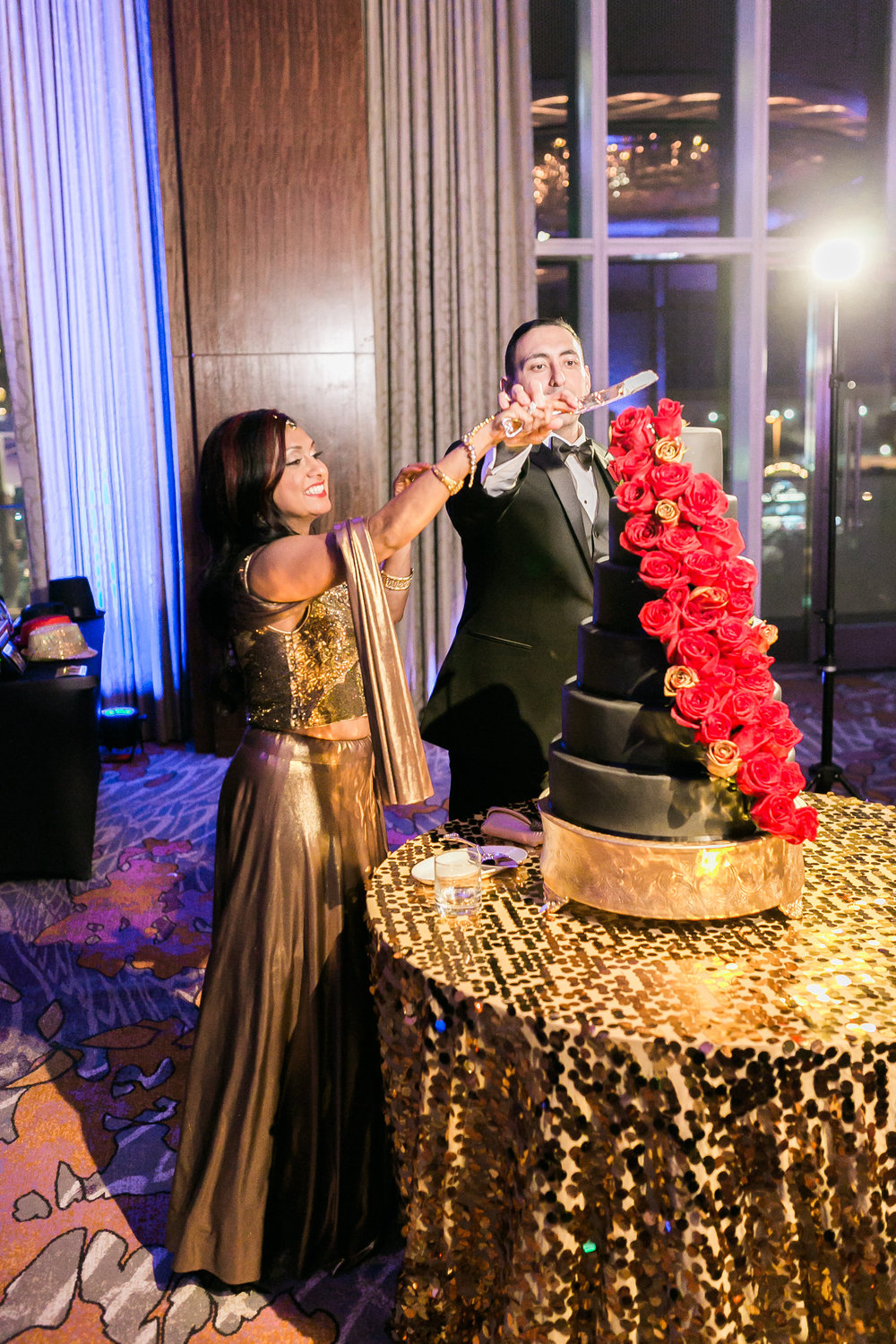 Cutting the cake in a saree.  Las Vegas Wedding Planner Andrea Eppolito shares this multicultural wedding.  Photo by J.Anne Photography. Wedding at Mandarin Oriental Las Vegas.  Decor by DBD Vegas.