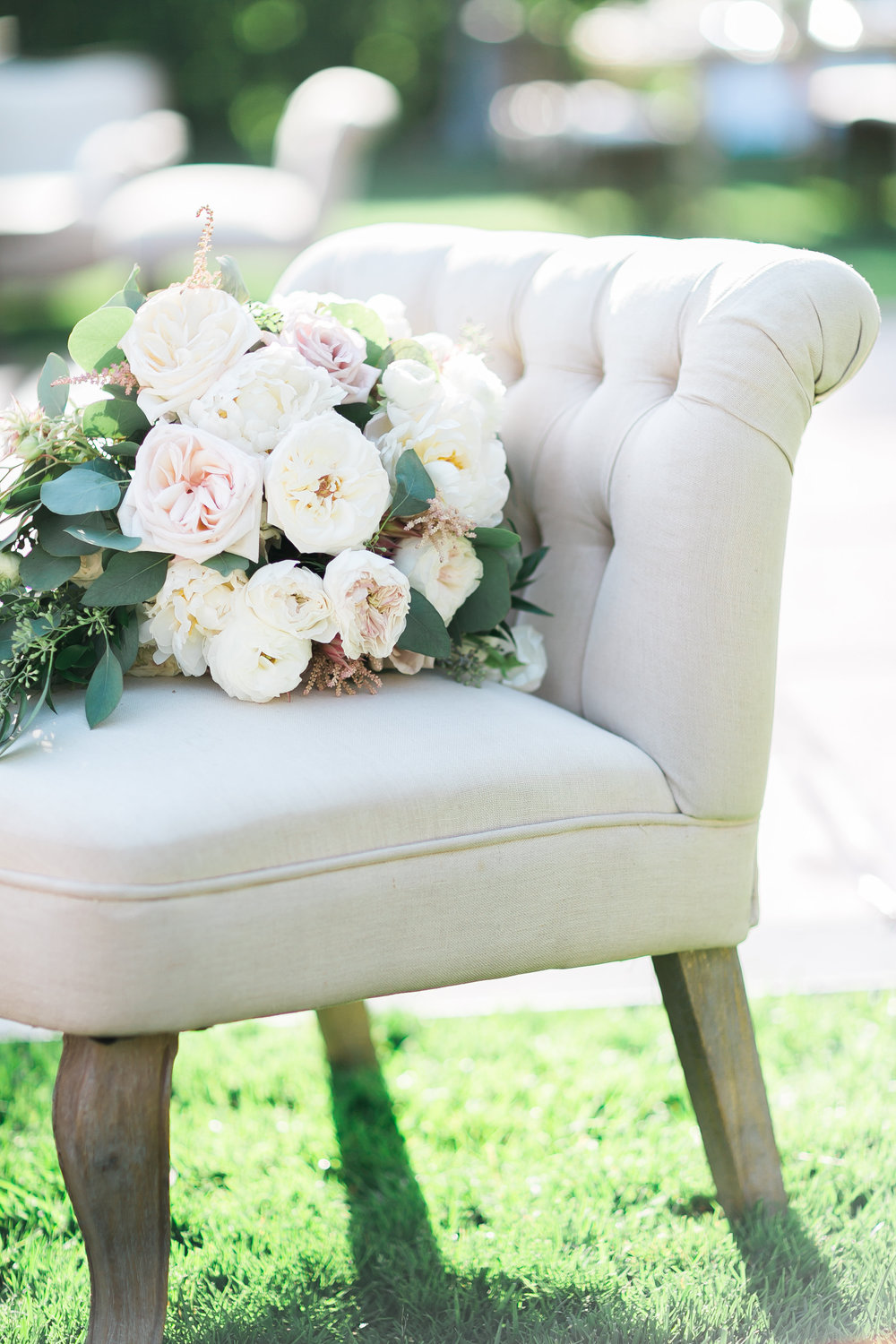 Garden bouquet on lounge chair at outdoor wedding.       Destination Wedding Planner  ANDREA EPPOLITO EVENTS   ·  Images by  J.ANNE P  HOTOOGRAPHY   ·  Video  HOO FILMS   ·  Venue Ritz Carlton Bacara Santa Barbara  · Gown MONIQUE LHULLIER  · Bridesmaids Dresses  SHOW ME YOUR MUMU  · Stationery  SHE PAPERIE  · Bride's Shoes  BADGLEY MISCHKA  · Hair and Makeup  TEAM HAIR AND MAKEUP  · Floral  BLUE MAGNOLIA  · Linen  LA TAVOLA  · Decor Rentals  TENT MERCHANT  · Calligraphy  EBB  ·Lighting  FIVE STAR AV  · Ice Cream Station  MCCONNELL'S ICE CREAM