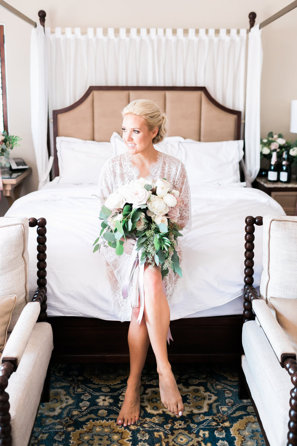 Blonde bride in robe with lush bouquet.   CREDITS:  Destination Wedding Planner  ANDREA EPPOLITO EVENTS  · Images by  J.ANNE P  HOTOGRAPHY  · Video  HOO FILMS  · Venue Ritz Carlton Bacara Santa Barbara ·Gown  MONIQUE LHULLIER ·Bridesmaids Dresses  SHOW ME YOUR MUMU ·Stationery  SHE PAPERIE ·Bride's Shoes  BADGLEY MISCHKA ·Hair and Makeup  TEAM HAIR AND MAKEUP · Floral  BLUE MAGNOLIA ·Linen  LA TAVOLA ·Decor Rentals  TENT MERCHANT ·Calligraphy  EBB ·Lighting  FIVE STAR AV ·Ice Cream Station  MCCONNELL'S ICE CREAM