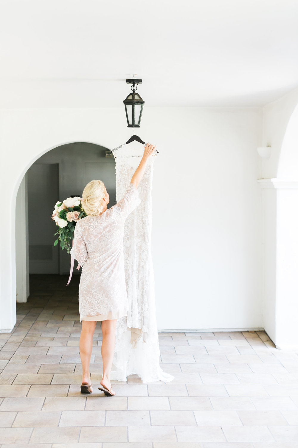 Bride taking wedding dress off hanger.   CREDITS:  Destination Wedding Planner  ANDREA EPPOLITO EVENTS  · Images by  J.ANNE P  HOTOGRAPHY  · Video  HOO FILMS  · Venue Ritz Carlton Bacara Santa Barbara ·Gown  MONIQUE LHULLIER ·Bridesmaids Dresses  SHOW ME YOUR MUMU ·Stationery  SHE PAPERIE ·Bride's Shoes  BADGLEY MISCHKA ·Hair and Makeup  TEAM HAIR AND MAKEUP · Floral  BLUE MAGNOLIA ·Linen  LA TAVOLA ·Decor Rentals  TENT MERCHANT ·Calligraphy  EBB ·Lighting  FIVE STAR AV ·Ice Cream Station  MCCONNELL'S ICE CREAM