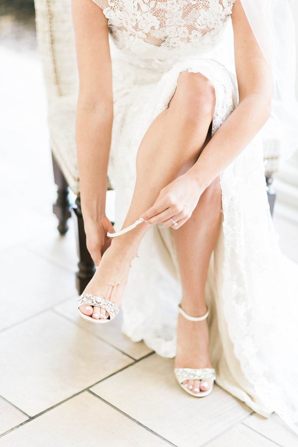 Bride putting on wedding shoes.    CREDITS:  Destination Wedding Planner  ANDREA EPPOLITO EVENTS   ·  Images by  J.ANNE P  HOTOGRAPHY   ·  Video  HOO FILMS   ·  Venue Ritz Carlton Bacara Santa Barbara  · Gown  MONIQUE LHULLIER  · Bridesmaids Dresses  SHOW ME YOUR MUMU  · Stationery  SHE PAPERIE  · Bride's Shoes  BADGLEY MISCHKA  · Hair and Makeup  TEAM HAIR AND MAKEUP  · Floral  BLUE MAGNOLIA  · Linen  LA TAVOLA  · Decor Rentals  TENT MERCHANT  · Calligraphy  EBB  ·Lighting  FIVE STAR AV  · Ice Cream Station  MCCONNELL'S ICE CREAM