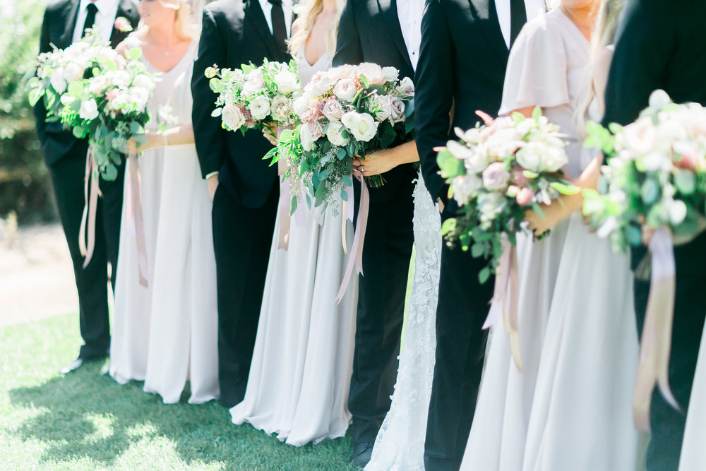 Bridesmaids and Groomsmen with Bouquets.    CREDITS:  Destination Wedding Planner  ANDREA EPPOLITO EVENTS   ·  Images by  J.ANNE P  HOTOGRAPHY   ·  Video  HOO FILMS   ·  Venue Ritz Carlton Bacara Santa Barbara  · Gown  MONIQUE LHULLIER  · Bridesmaids Dresses  SHOW ME YOUR MUMU  · Stationery  SHE PAPERIE  · Bride's Shoes  BADGLEY MISCHKA  · Hair and Makeup  TEAM HAIR AND MAKEUP  · Floral  BLUE MAGNOLIA  · Linen  LA TAVOLA  · Decor Rentals  TENT MERCHANT  · Calligraphy  EBB  ·Lighting  FIVE STAR AV  · Ice Cream Station  MCCONNELL'S ICE CREAM