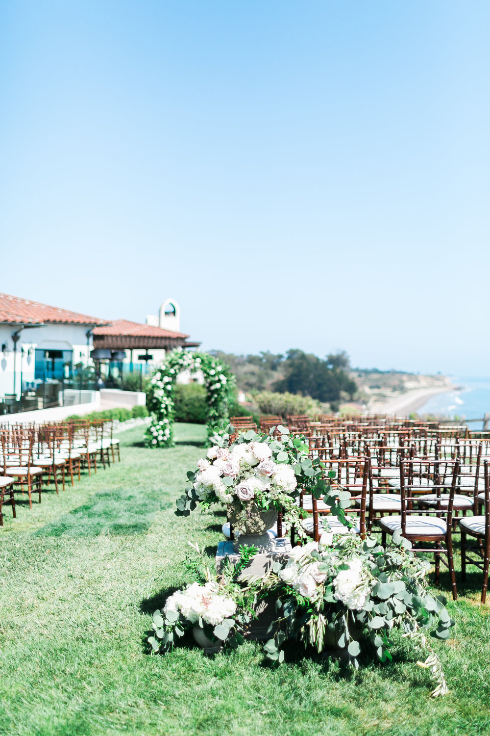 Wedding ceremony near the ocean.   CREDITS:  Destination Wedding Planner  ANDREA EPPOLITO EVENTS  · Images by  J.ANNE P  HOTOGRAPHY  · Video  HOO FILMS  · Venue Ritz Carlton Bacara Santa Barbara ·Gown  MONIQUE LHULLIER ·Bridesmaids Dresses  SHOW ME YOUR MUMU ·Stationery  SHE PAPERIE ·Bride's Shoes  BADGLEY MISCHKA ·Hair and Makeup  TEAM HAIR AND MAKEUP · Floral  BLUE MAGNOLIA ·Linen  LA TAVOLA ·Decor Rentals  TENT MERCHANT ·Calligraphy  EBB ·Lighting  FIVE STAR AV ·Ice Cream Station  MCCONNELL'S ICE CREAM