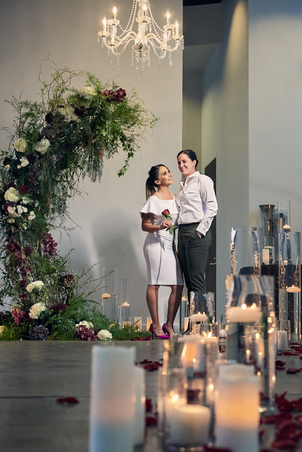 Two brides to be getting engaged under a chandelier.  Las Vegas Wedding Planner Andrea Eppolito designed the surprise engagement at the Mandarin Oriental for two brides to be.  Decor and lighting by Flora Couture and LED Unplugged, with photos by Fabio and Adri.