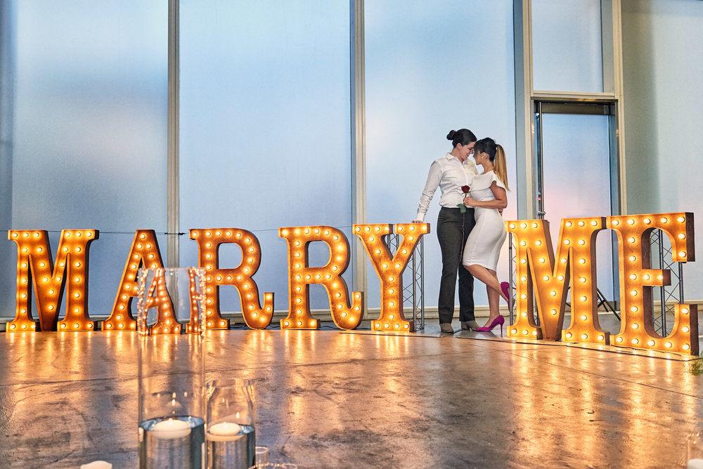 Marry Me in Big Lights for a proposal.  Las Vegas Wedding Planner Andrea Eppolito designed the surprise engagement at the Mandarin Oriental for two brides to be.  Decor and lighting by Flora Couture and LED Unplugged, with photos by Fabio and Adri.