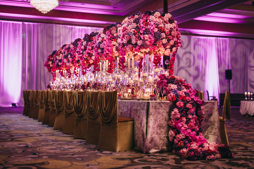 This long table features over the top centerpieces in shades of purple, with capped garland at the end.  Photo by Adam Trujillo.  Purple wedding.